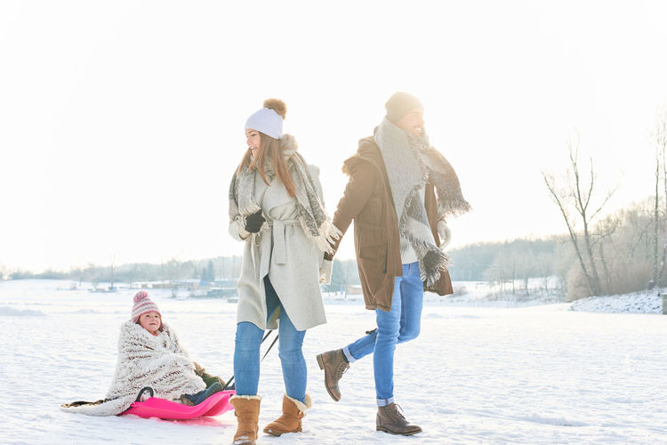 Family enjoying on snow covered landscape during winter