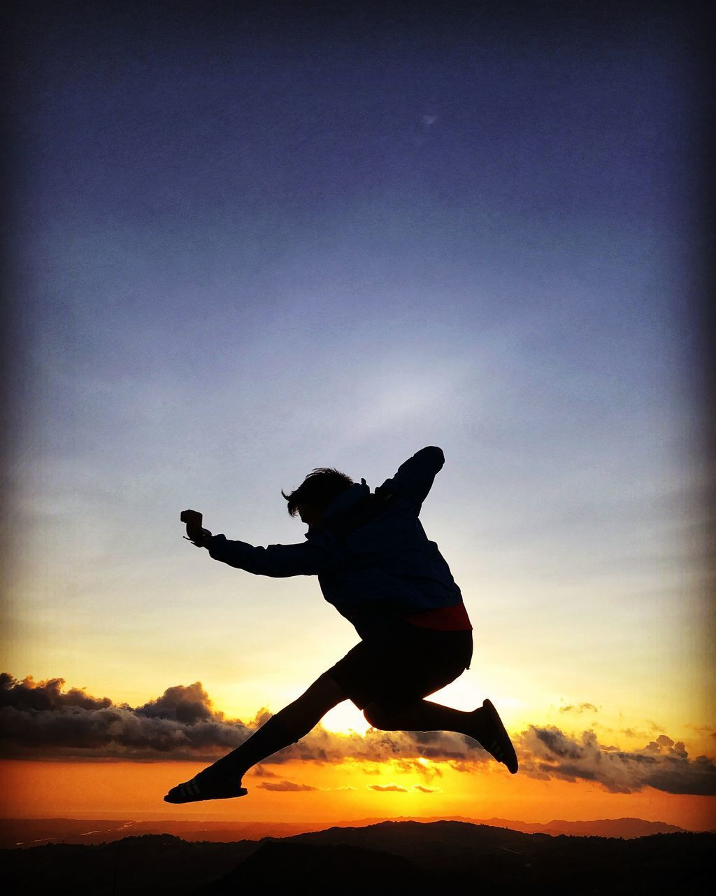 sky, one person, sunset, silhouette, real people, leisure activity, lifestyles, full length, men, orange color, human arm, nature, cloud - sky, jumping, sport, vitality, beauty in nature, side view, skill, outdoors, excitement, arms raised