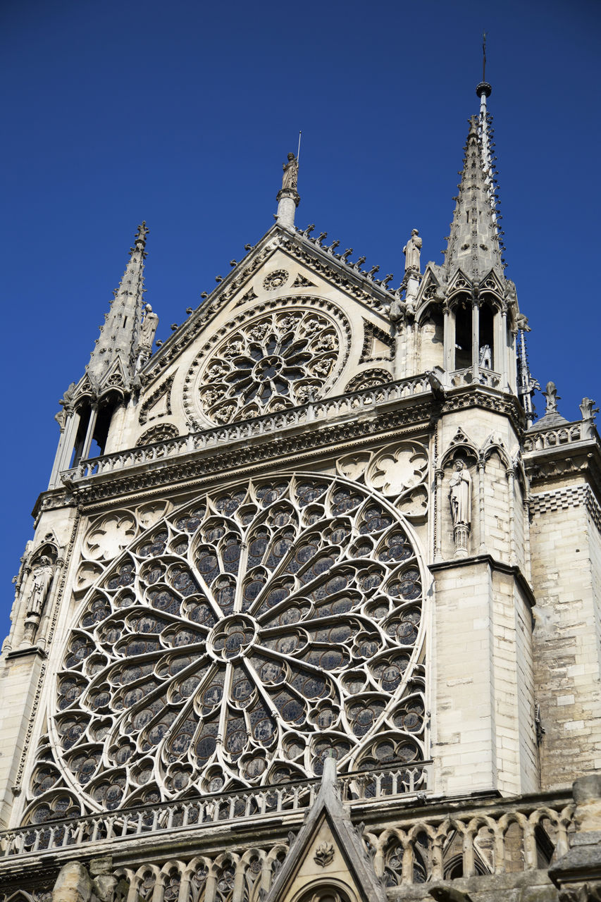 religion, spirituality, place of worship, low angle view, architecture, rose window, built structure, building exterior, day, outdoors, no people, history, travel destinations, clear sky, sky