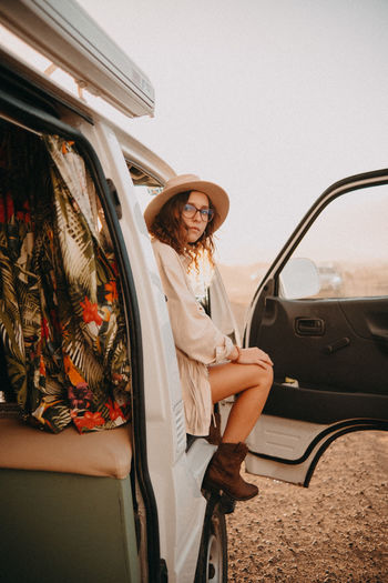 Portrait of woman standing by car