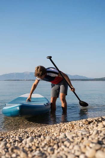Man with paddleboard and oar standing in lake against clear sky