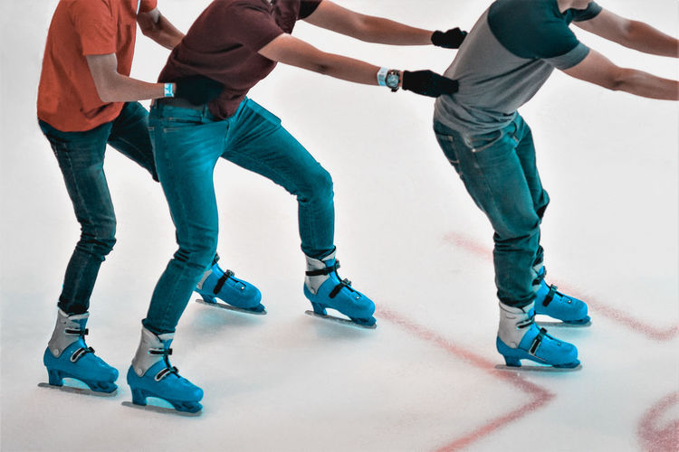 Low section of male friends ice-skating on rink