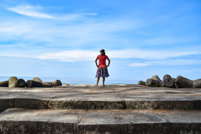Rear view of woman standing on rock against sky