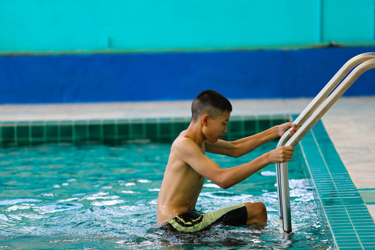 Full length of shirtless boy in swimming pool