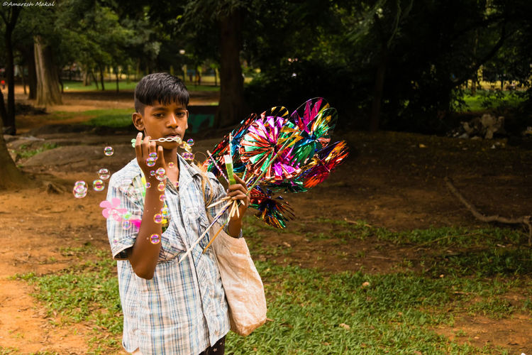 That's life ! Boy Bubbles Chiild Labour Child Vendor Childhood Colourful Cubbonparkbangalore Elementary Age Focus On Foreground Human Face Nature Outdoors Park - Man Made Space Person Poor Kids Poority Portrait Photography Streetphotography Tree Vibrant Colors Water Bubbles