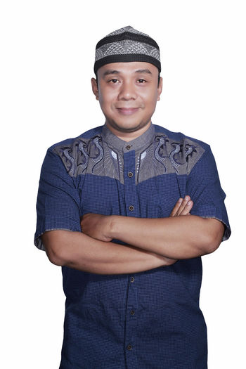Portrait Smiling asian muslim man crossed his hand on white background Arms Crossed Casual Clothing Cut Out Front View Looking At Camera One Person People Portrait Real People Smiling Standing Studio Shot White Background Young Adult