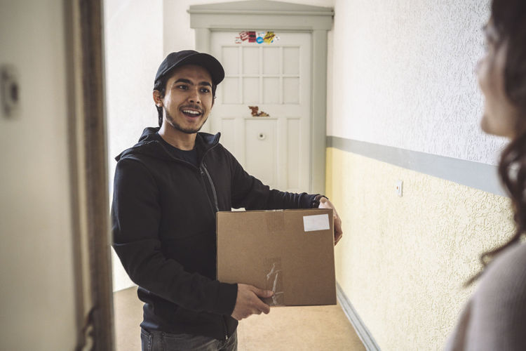 Portrait of smiling young man standing against door at home