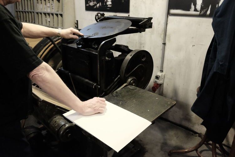 Midsection of typesetter using machinery while working in workshop