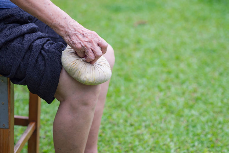 Elderly woman having use thai herbal compress ball on knee.