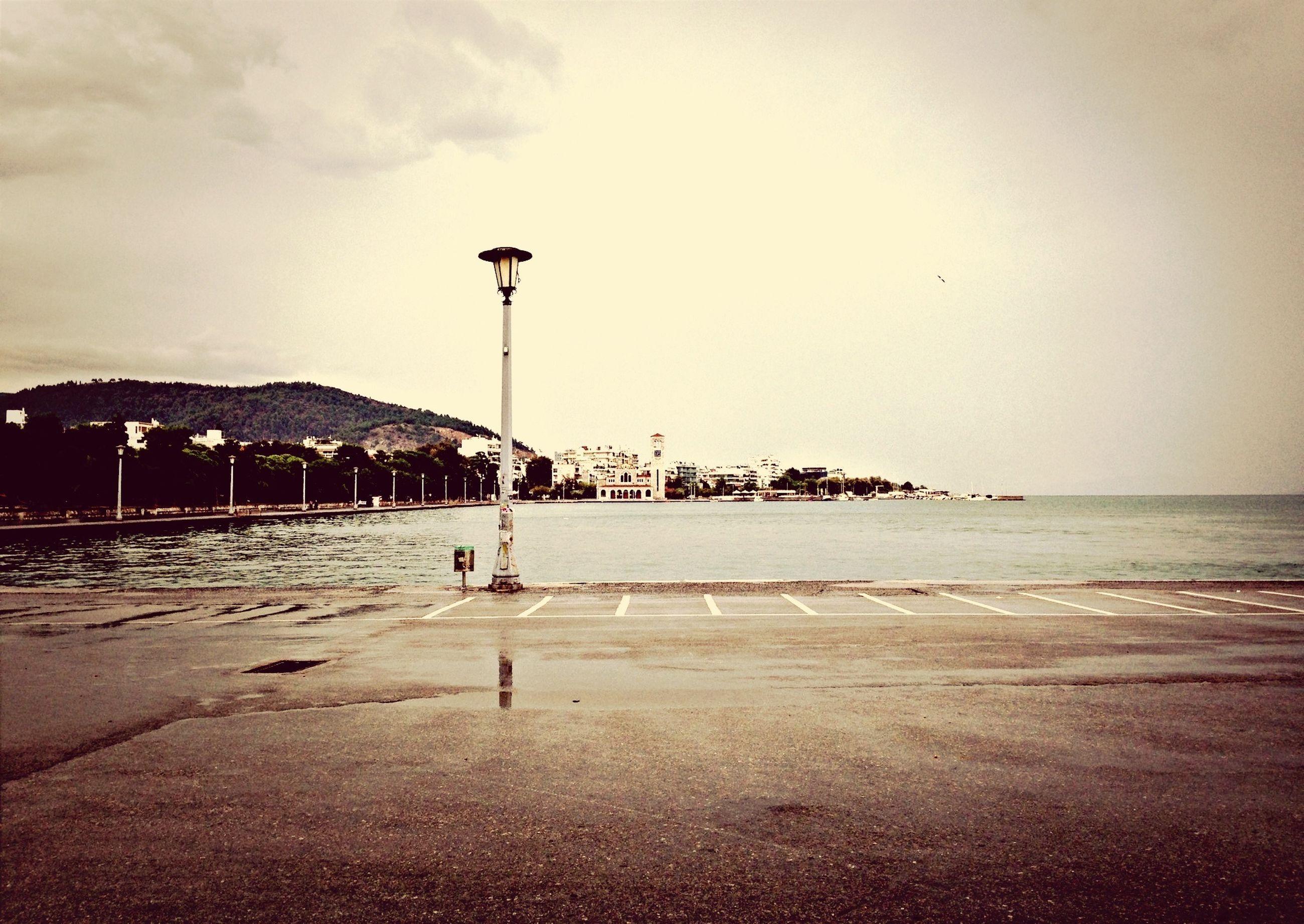 sea, beach, water, shore, sand, sky, horizon over water, street light, scenics, tranquility, tranquil scene, beauty in nature, nature, incidental people, idyllic, coastline, outdoors, cloud - sky, lighting equipment, silhouette