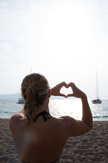 Rear view of woman making heart shape on beach against sky
