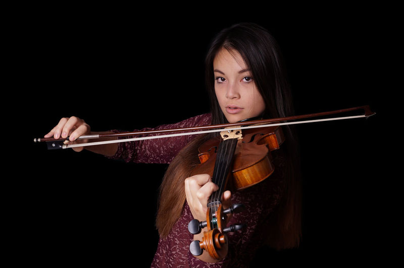 Portrait of young woman playing violin against black background