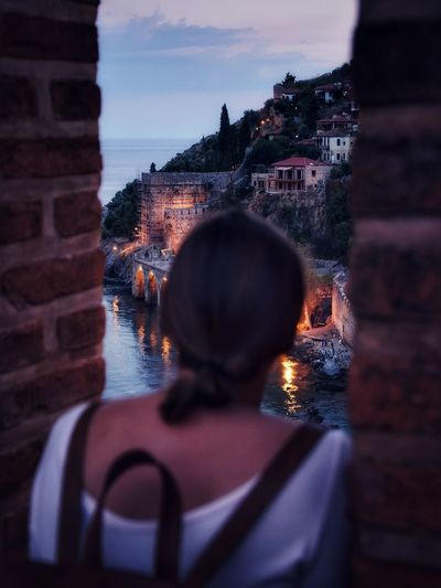 Rear view of woman looking at buildings during sunset