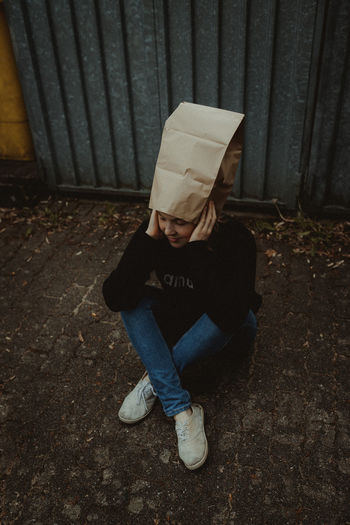 High Angle View Of Woman Wearing Paper Bag Sitting Against Wall