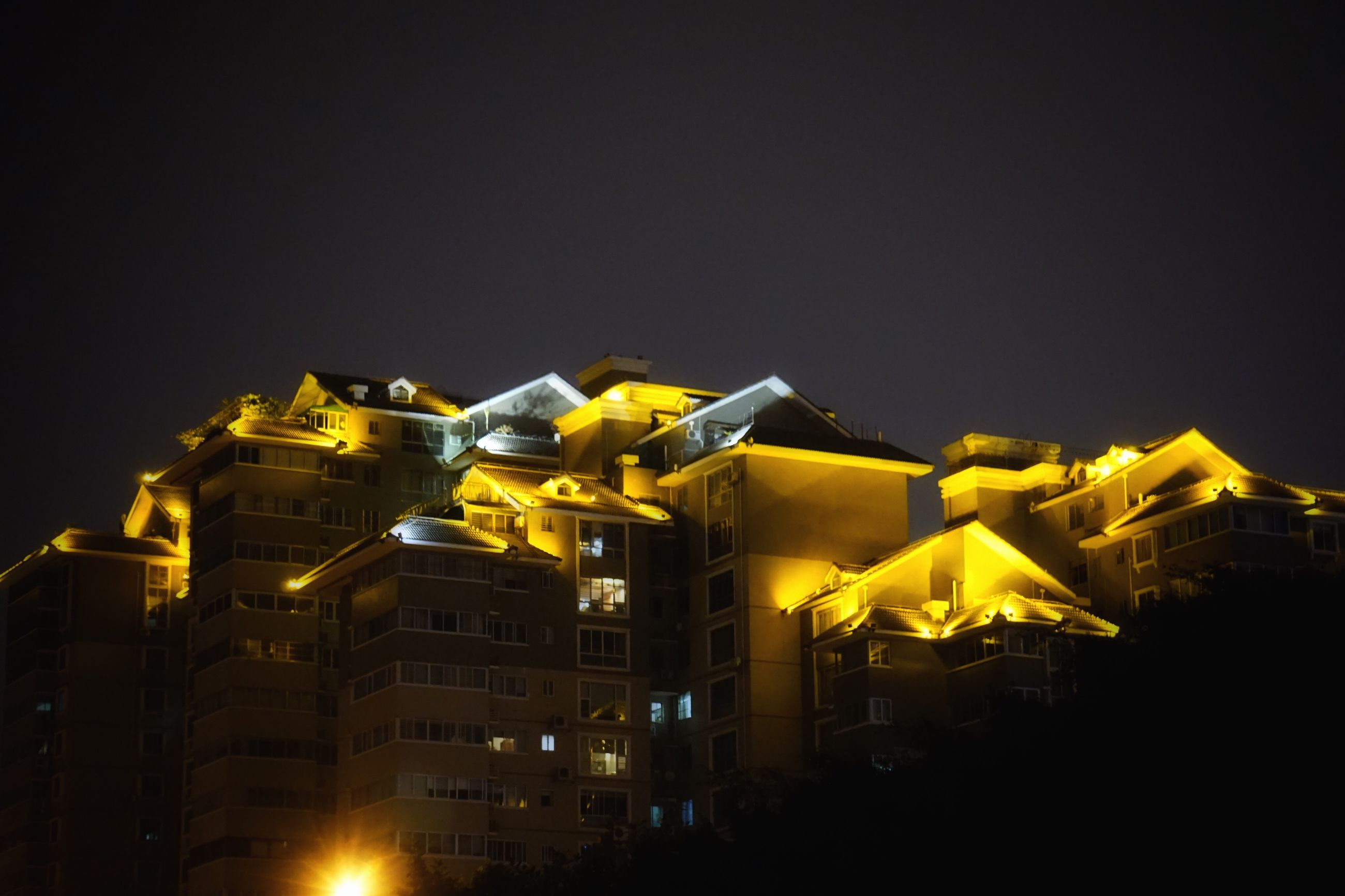 architecture, building exterior, built structure, illuminated, night, city, residential building, low angle view, clear sky, yellow, travel destinations, apartment, sky, outdoors, city life, residential district, facade, no people, tourism, spire, building story