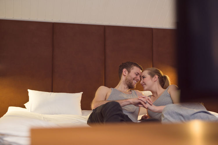 Young couple sitting on bed