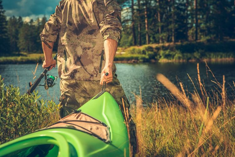 Caucasian Fly Fisherman Wearing Camouflage with Kayak Going Toward the River. Fly Fishing Kayaking Norway Recreation  Adult Boat Day Fishing Grass Holding Kayak Lake Land Leisure Activity Lifestyles Men Nature One Person Outdoors Plant Real People Standing Three Quarter Length Tree Water