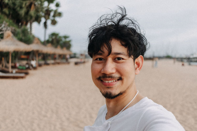 Portrait of smiling young man on beach