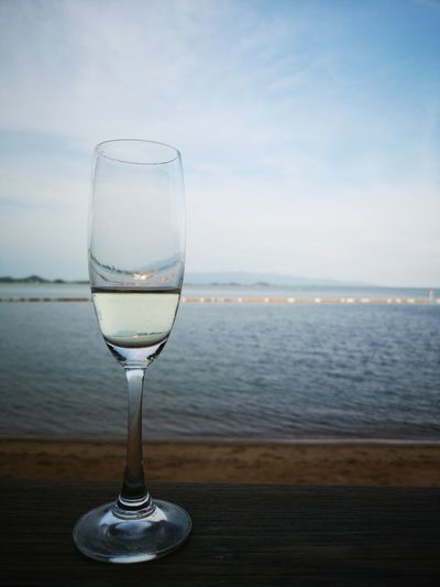 Drinking glass on table by sea against sky