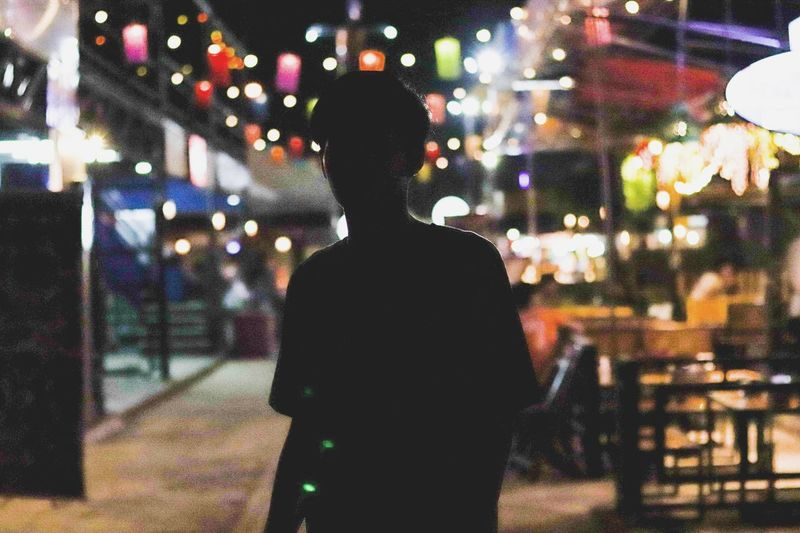 Silhouette man standing against illuminated sidewalk cafe at night
