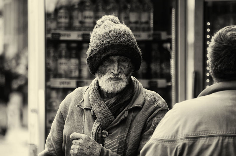 Portrait of man wearing hat in city during winter
