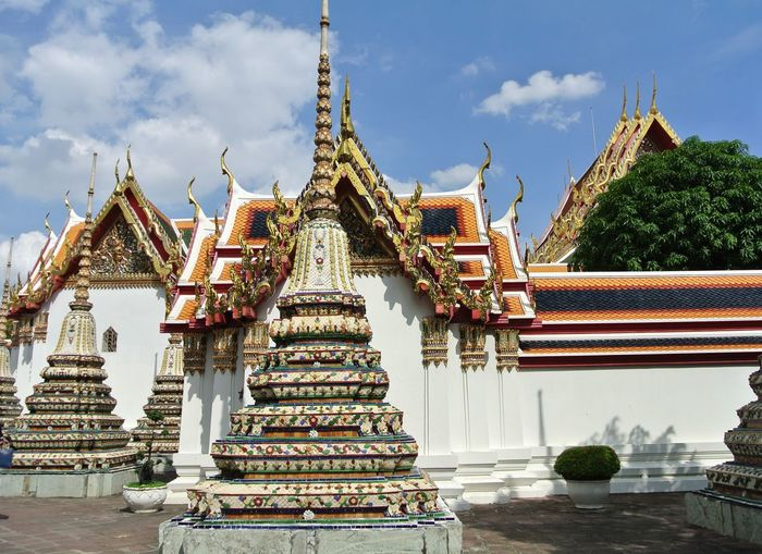 Pagoda is in Wat Pho that was named as the temple of the pagoda or chedi that are decorated with yellow glaze or glazed tiles or dark blue Architecture Art And Craft Belief Building Building Exterior Built Structure Cloud - Sky Day Nature No People Ornate Outdoors Place Of Worship Plant Religion Sky Spire  Spirituality Tree