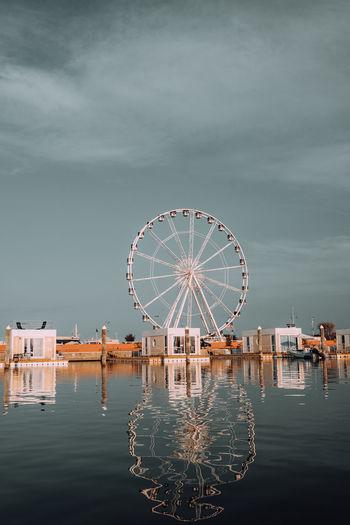 Ferris wheel by lake against sky