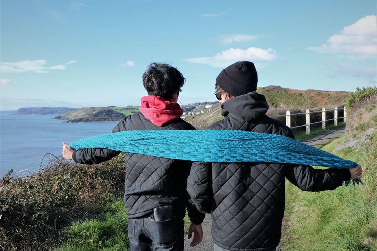 Rear view of friends holding scarf while standing on hill by sea against sky