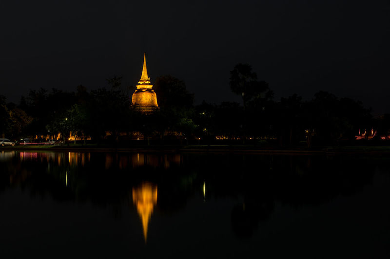Ancient temples in sukhothai Buddha Buddhist Temple Thailand Reflection Architecture Built Structure Illuminated Water Night Building Exterior Sky Place Of Worship Belief Building Lake Waterfront Religion Spirituality Tree Travel Destinations No People Outdoors