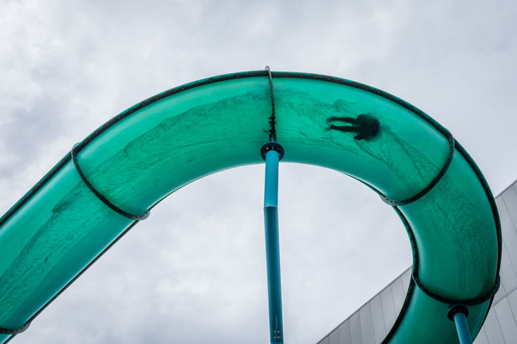 Low angle view of men in water park ride against sky