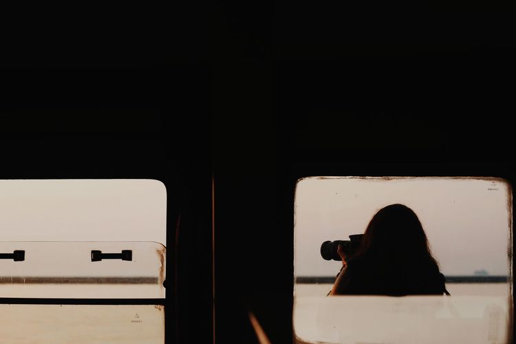 Rear view of woman photographing in bus