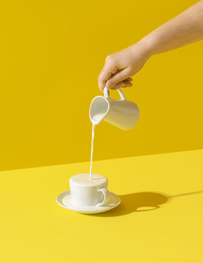 Woman pouring milk from a jug, in bright light, isolated on yellow background. milk dripping.