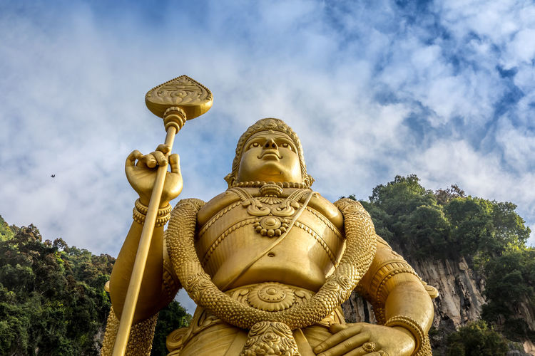 Low angle view of golden statue and trees against cloudy sky