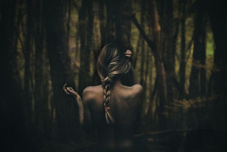 Rear view of sensual woman standing against forest