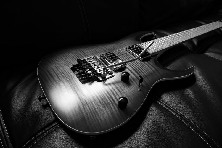 High angle view of guitar on sofa