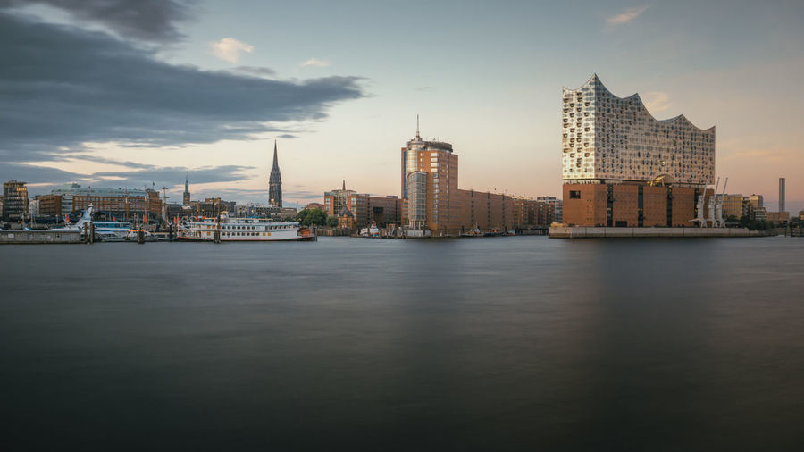 City By River Against Sky At Dusk