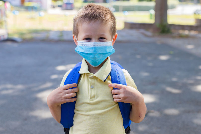 Boy wearing a protective mask with a backpack behind his back in the schoolyard