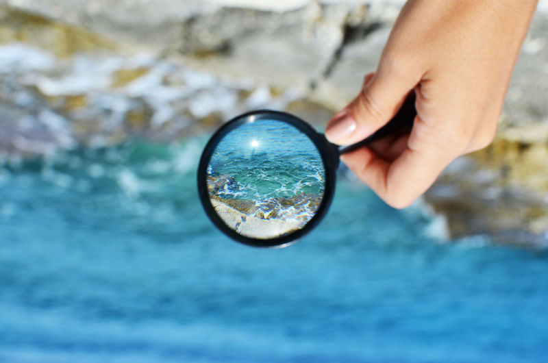 Cropped image of woman's hand holding magnifying glass over sea waves