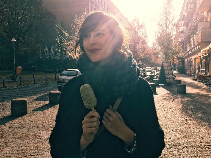 Smiling Young Woman Holding Ice Cream Against Buildings On Sunny Day