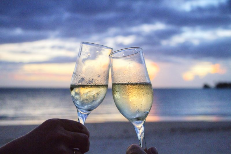 Human Hand Water Wineglass Sea Alcohol Drink Champagne Wine Drinking Glass Sunset Beverage Personal Perspective Celebratory Toast
