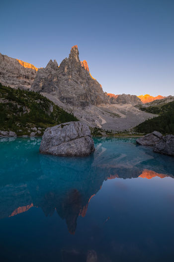 Morning light lighting up the mountains behind the Lago di Sorapis Beauty In Nature Blue Calm Clear Sky Dawn Day Dolomites Dolomiti Italy Lake Majestic Morning Mountain Nature Outdoors Reflection Rock Formation Scenics Sunrise Tranquility Travel Travel Destinations Trekking Water