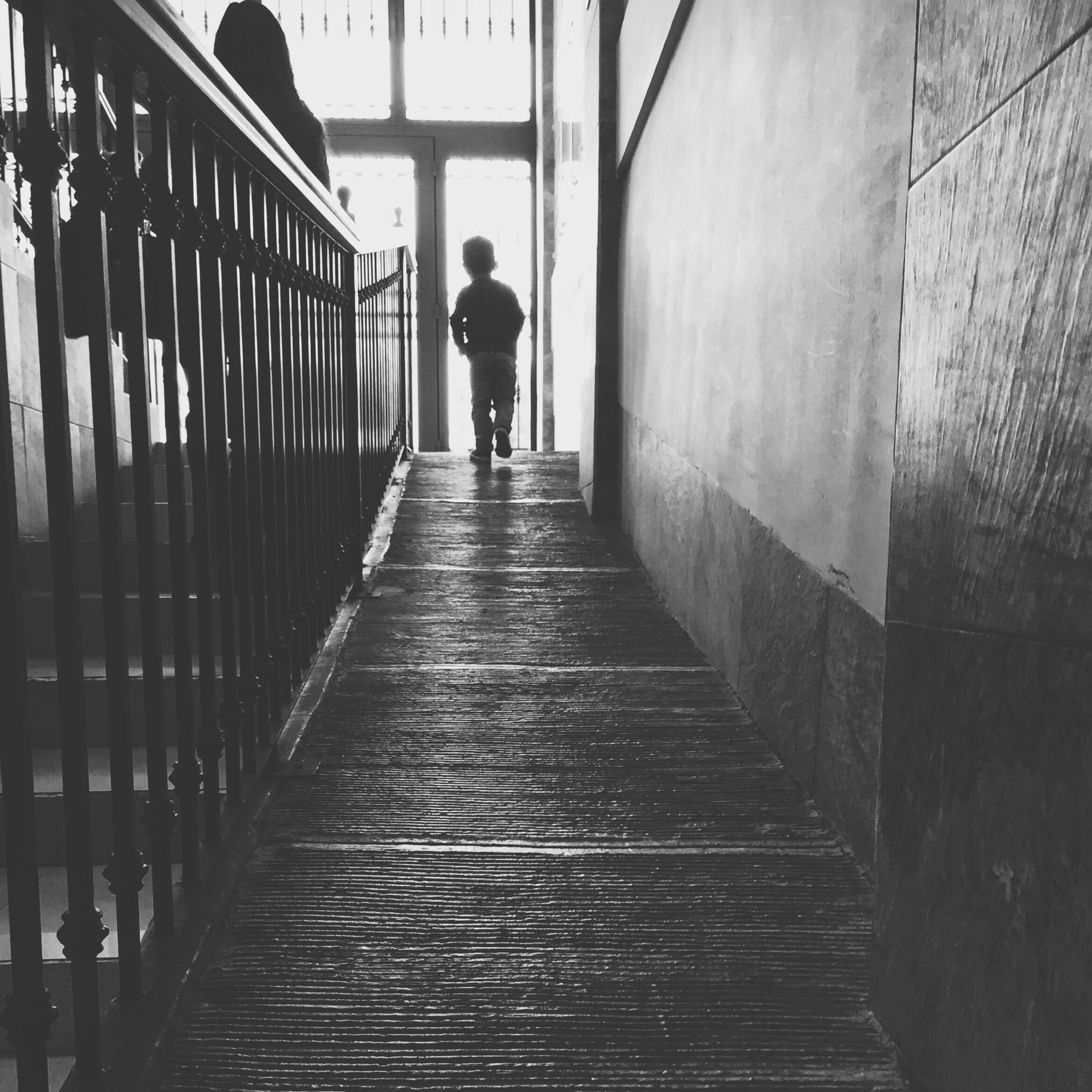 architecture, full length, built structure, rear view, walking, the way forward, men, lifestyles, indoors, railing, silhouette, corridor, leisure activity, standing, person, unrecognizable person, wall - building feature, day