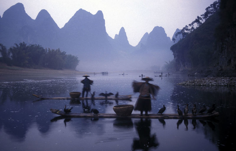 Blurred Motion Of People On Boat In River With Reflection Against Mountains