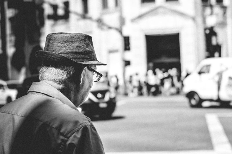 Midsection of man wearing hat on street in city