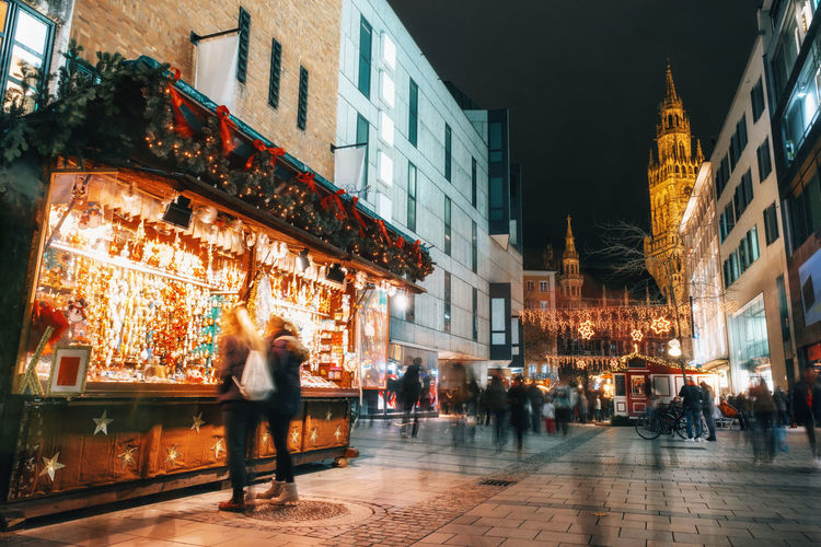 Blurred moved people and sales booth at the Christmas market in Munich, Germany Christmas Lights Architecture Blurred Motion Building Exterior Christmas Market Christmastime City Illuminated Leisure Activity Lifestyles Night Outdoors Real People Street