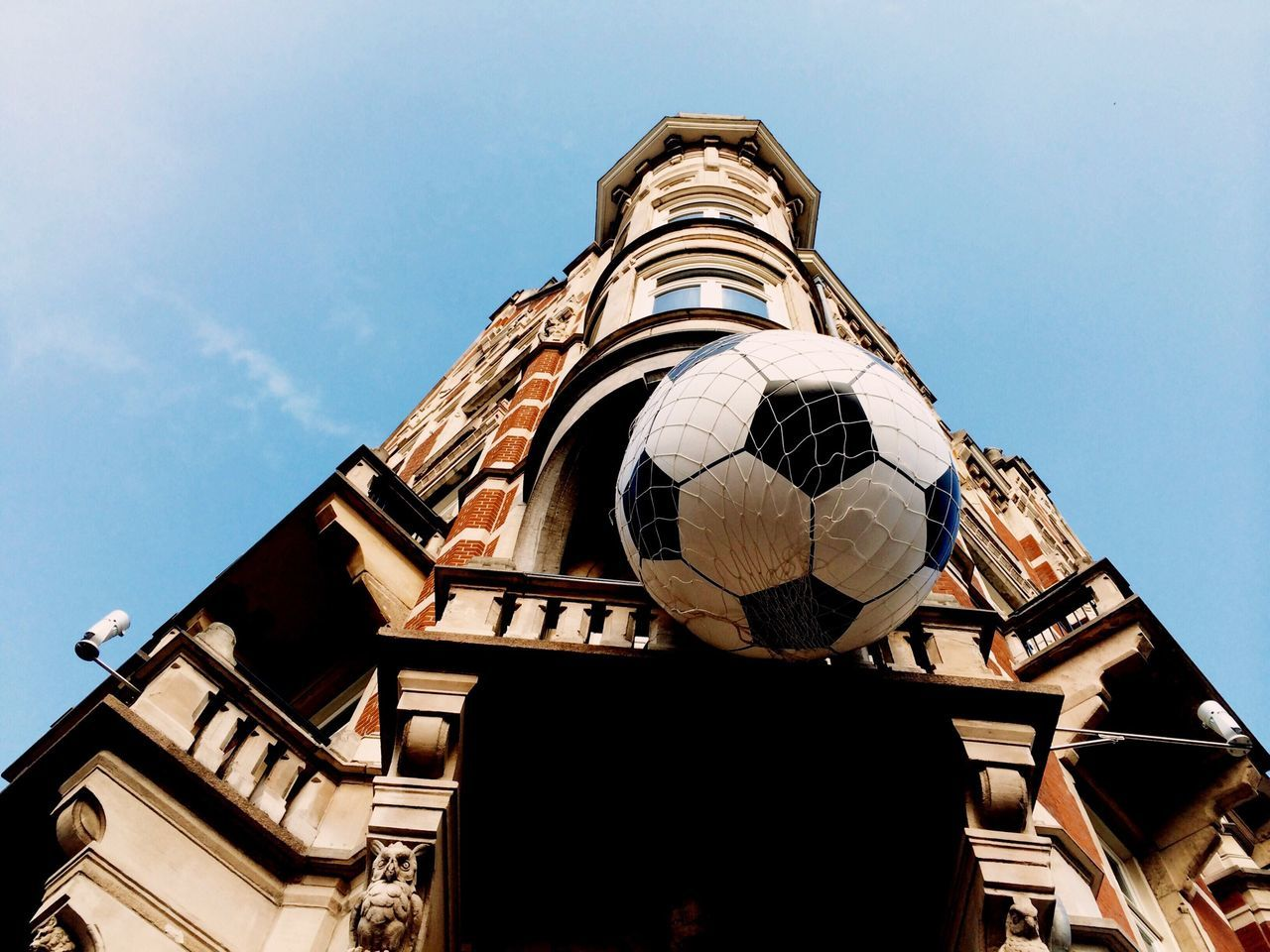 Low angle view of building with large soccer ball hanging in net