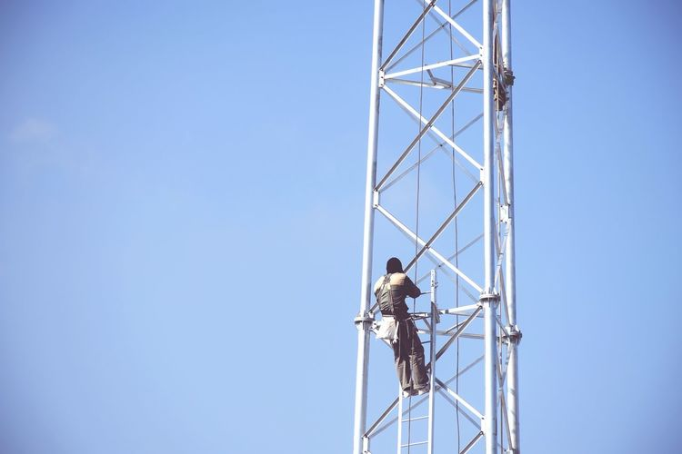 Low angle view of man working against clear blue sky