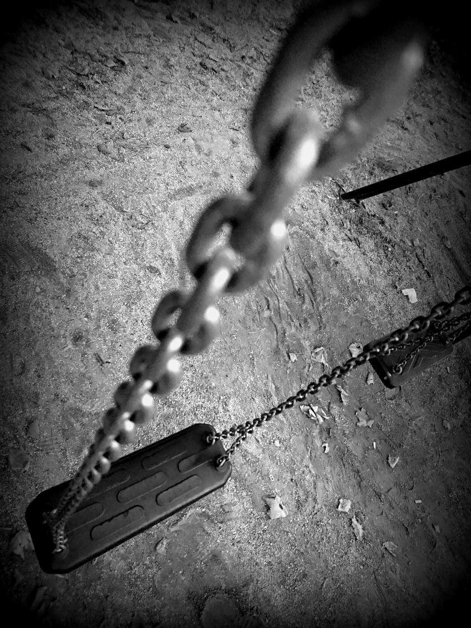 CLOSE-UP OF CHAIN HANGING AGAINST WALL