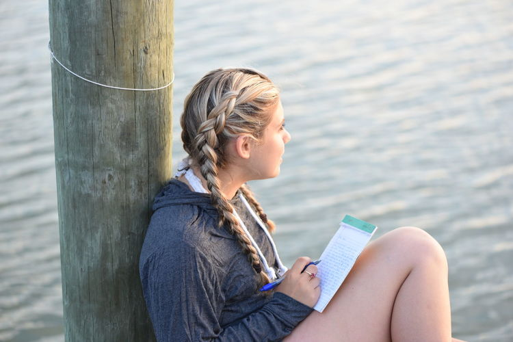 High Angle View Of Thoughtful Teenage Girl Writing On Note Pad While Sitting By Lake
