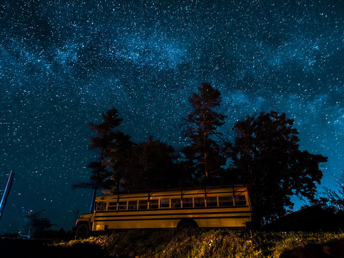 Low Angle View Of Bus By Trees Against Star Field At Night